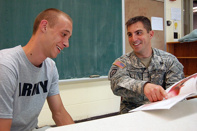 Staff Sgt. Nicholas Dimiceli, Milwaukee Recruiting Battalion, reunites with Jacob Beringer, a school buddy from a decade ago at St. Agnes School in Butler, Wisconsin. Dimiceli was an eighth grader who read books and did various activities with Beringer who was then a first grader. They sit in a classroom where they both went through eighth grade. Beringer is now joining the Army following his reunion with Dimiceli.