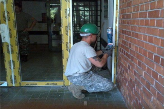 Sgt. Jeffrey Grimes, 412th Engineer Company based Scranton, Pa., works alongside Macedonia Soldiers and contractors to renovate the doors and windows of the kindergarten Femo Kulakov in Negotino, Macedonia, Aug. 4-26. (U.S. Army photo by Master Sgt. Darryl Cheatham)