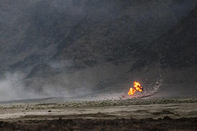 An artillery round detonates at the base of a remote hill south of Kandahar Airfield, Afghanistan, fired by Alpha Battery, 2nd Battalion, 77th Field Artillery Regiment, 4th Infantry Brigade Combat Team, 4th Infantry Division, Aug. 22, 2014. The round was part of a shoot to register, or zero, the howitzers, which had just arrived on Kandahar Airfield from Forward Operating Base Pasab. The shoot also provided training for a fire support team from 1st Battalion, 12th Infantry Regiment, 4th Infantry Brigade Combat Team, 4th Infantry Division.