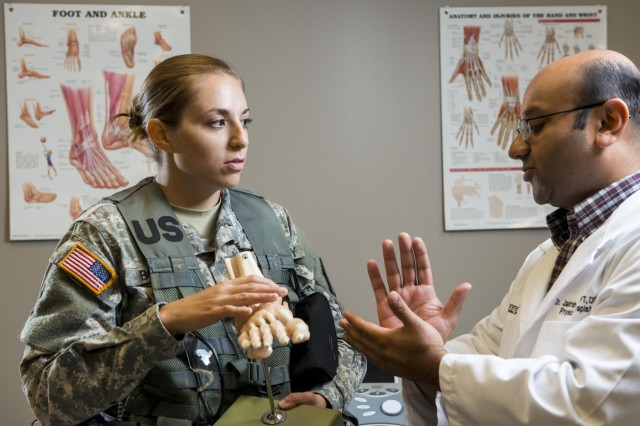Second Lt. Nicole Boda, Army Reserve officer with the 863rd Engineer Battalion, interacts with Dr. Jaimin G. Shah, physical therapist with the health and wellness division at the Argonne National Laboratory in Darien, Ill., as part of a photo shoot that promotes Citizen-Soldiers in the science, technology, engineering and math industries. (U.S. Army photo by Sgt. 1st Class Michel Sauret)