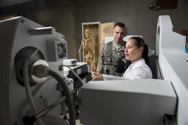 Spc. Kevin Thomas, Army Reserve Soldier with the 863rd Engineer Battalion, interacts with Joni Garcia Hunter, physical therapy assistant with the health and wellness division at the Argonne National Laboratory in Darien, Ill., while she explains different components of an X-ray machine as part of a photo shoot that promotes Citizen-Soldiers in the science, technology, engineering and math industries. (U.S. Army photo by Sgt. 1st Class Michel Sauret)