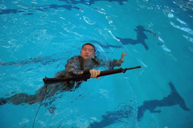 Cadet Sean Lee holds his training weapon as he swims during combat water survival training as part of his Army ROTC requirements at Vanderbilt University, Nashville. Lee recently was awarded first place for his research and oral presentation on a new to treatment for glaucoma during the Southeastern Medical Scientist Symposium at Emory University School of Medicine, Atlanta, August 23.