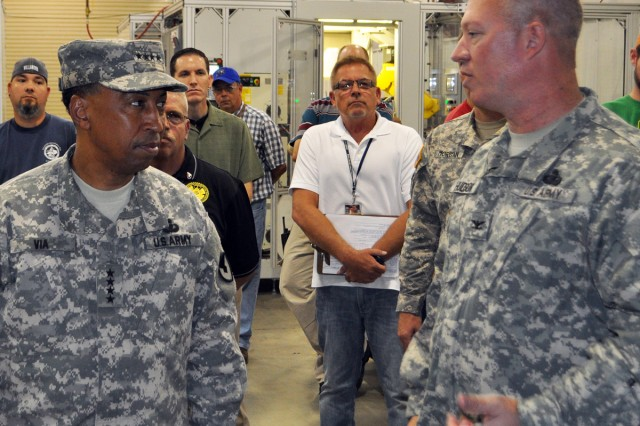Blue Grass Army Depot Commander, Col. Lee G. Hudson (right) discusses the hi-tech robotic process of installing grenade confidence clips during a visit by Army Materiel Command CG, Gen. Dennis L. Via Aug. 27, 2014