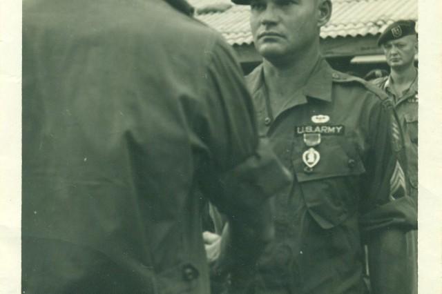 Lt. Col. Ken Facey presents the Purple Heart to then-Sgt. 1st Class Bennie G. Adkins, in 1966, in Vietnam.