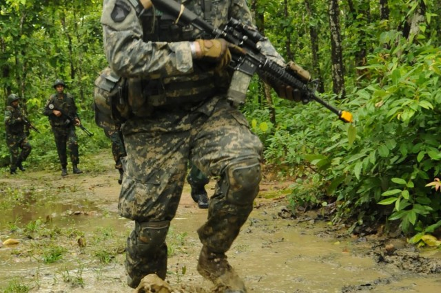 Staff Sgt. Vance Meier, an infantryman squad leader with Comanche Company, 1st Battalion (Airborne), 501st Infantry Regiment, 4th Infantry Brigade Combat Team (Airborne), 25th Infantry Division, runs through a muddy area in the jungle Aug. 26, 2014, at the Rajendrapur Catonement Training Area, near Dhaka, Bangladesh. Meier was in Bangladesh for Aurora Monsoon, a bilateral exchange and training exercise focused on building relationships and enhancing abilities in operating in a jungle environment and unfamiliar terrain. (U.S. Army photo by Sgt. 1st Class Jeffrey Smith/Released)
