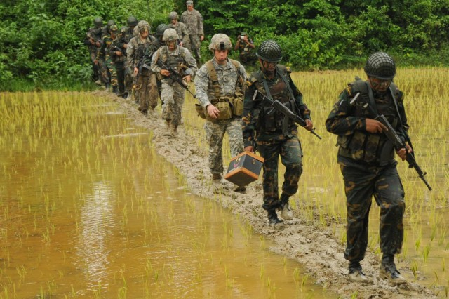 U.S. Army paratroopers with the 1st Battalion (Airborne), 501st Infantry Regiment, 4th Infantry Brigade Combat Team (Airborne), 25th Infantry Division, along with soldiers of the Bangladesh Army's 46th Independent Infantry Brigade move in a file formation across rice fields during a tactical training exercise Aug. 26, 2014, at the Rajendrapur Catonement Training Area, near Dhaka, Bangladesh. The Geronimos were in Bangladesh for Aurora Monsoon, a bilateral exchange and training exercise focused on building relationships and enhancing abilities in operating in a jungle environment and unfamiliar terrain. (U.S. Army photo by Sgt. 1st Class Jeffrey Smith/Released)