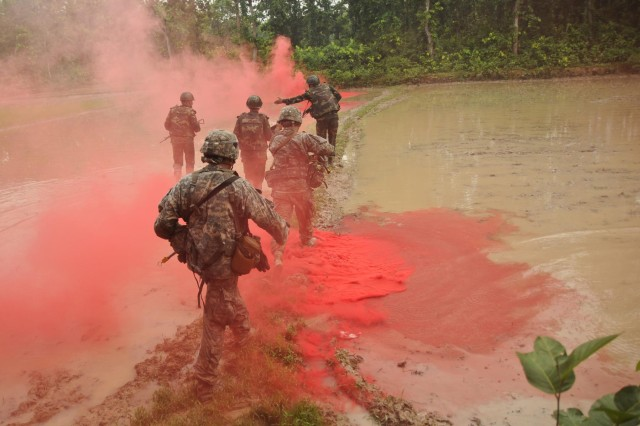 U.S. Army paratroopers with the 1st Battalion (Airborne), 501st Infantry Regiment, 4th Infantry Brigade Combat Team (Airborne), 25th Infantry Division, along with soldiers of the Bangladesh Army's 46th Independent Infantry Brigade move in a file formation under the concealment of smoke across rice fields during a tactical training exercise Aug. 26, 2014, at the Rajendrapur Catonement Training Area, near Dhaka, Bangladesh. The Geronimos were in Bangladesh for Aurora Monsoon, a bilateral exchange and training exercise focused on building relationships and enhancing abilities in operating in a jungle environment and unfamiliar terrain. (U.S. Army photo by Sgt. 1st Class Jeffrey Smith/Released)