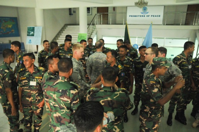 Paratroopers with the 1st Battalion (Airborne), 501st Infantry Regiment, 4th Infantry Brigade Combat Team (Airborne), 25th Infantry Division, socialize with soldiers from the Bangladesh Army's 46th Independent Infantry Brigade during a social event Aug. 23, 2014, at the Bangladesh Institute of Peace Support Operation Training at the Rajendrapur Catonement Training Area, near Dhaka, Bangladesh. The U.S. Army was in Bangladesh for Aurora Monsoon, a bilateral exchange and training exercise focused on building relationships and enhancing abilities in operating in a jungle environment and unfamiliar terrain. (U.S. Army photo by Sgt. 1st Class Jeffrey Smith/Released)