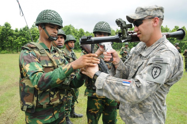 Capt. Bradley Benjamin (right), commander of Delaware Company, 1st Battalion (Airborne), 501st Infantry Regiment, 4th Infantry Brigade Combat Team (Airborne), 25th Infantry Division, peers through the sites of a Bangladesh Army 40 mm rocket launcher as Bangladesh soldiers with the 46th Independent Infantry Brigade instruct him on its components Aug. 26, 2014, at the Rajendrapur Catonement Training Area, near Dhaka, Bangladesh. Benjamin and the U.S. Army were in Bangladesh for Aurora Monsoon, a bilateral exchange and training exercise focused on building relationships and enhancing abilities in operating in a jungle environment and unfamiliar terrain. (U.S. Army photo by Sgt. 1st Class Jeffrey Smith/Released)