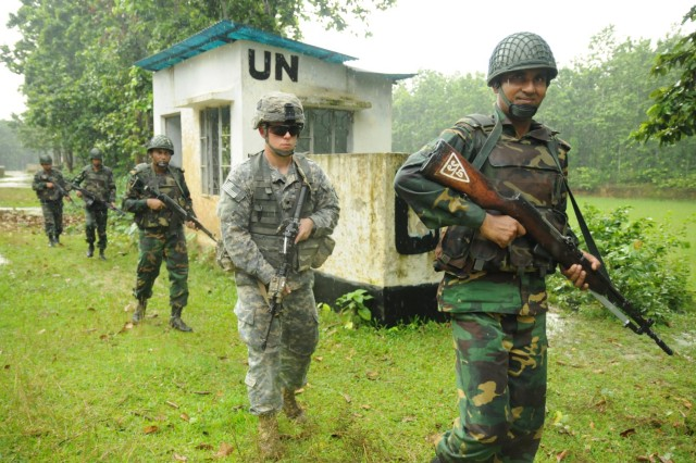A paratrooper with the 1st Battalion, 501st Infantry Regiment (Airborne), 4th Infantry Brigade Combat Team (Airborne), 25th Infantry Division, moves in a file formation with soldiers of the Bangladesh Army's 46th Independent Infantry Brigade during a tactical training exercise Aug. 26, 2014, at the Rajendrapur Catonement Training Area, near Dhaka, Bangladesh. The U.S. Army was in Bangladesh for Aurora Monsoon, a bilateral exchange and training exercise focused on building relationships and enhancing abilities in operating in a jungle environment and unfamiliar terrain. (U.S. Army photo by Sgt. 1st Class Jeffrey Smith/Released)