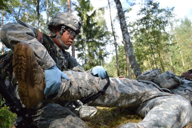Spc. Joey Guzman, assigned to 421st Multifunctional Medical Battalion, applies a tourniquet, while under simulated direct fire, to the leg of a simulated gunshot victim in order to prepare him for movement to safety and further Tactical Combat Casualty Care during Combat Testing Lane 1, at Camp Aachen in the Grafenwoehr Training Area, Germany.
