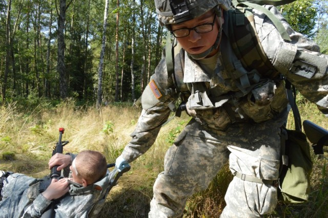 Spc. Kyle Benjamin, assigned to 421st Multifunctional Medical Battalion, drags his battle buddy to safety behind a natural barrier to provide further medical care during simulated direct fire, at Camp Aachen in the Grafenwoehr Training Area, Germany.