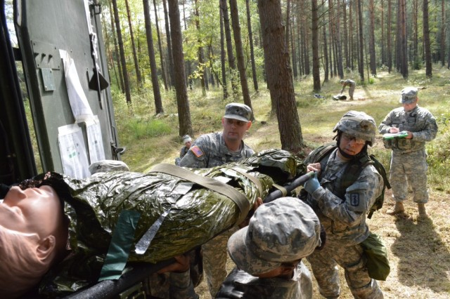 Chief Warrant Officer 2 Vladimir Sequera, assigned to 421st Multifunctional Medical Battalion, loads and secures simulated patients into a Field Litter Ambulance during Combat Testing Lane 2 of the U.S. Army Europe Expert Field Medical Badge qualification, at Camp Aachen in the Grafenwoehr Training Area, Germany.