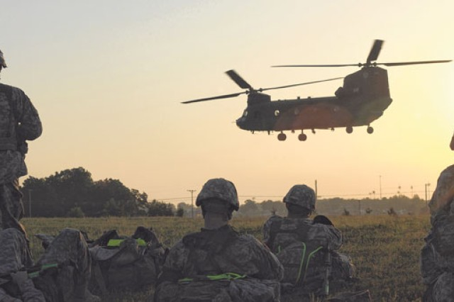 Competitors watch the sun rise, as they wait for their turn to board the Chinook helicopter and fly to their first event on the second day of the competion.