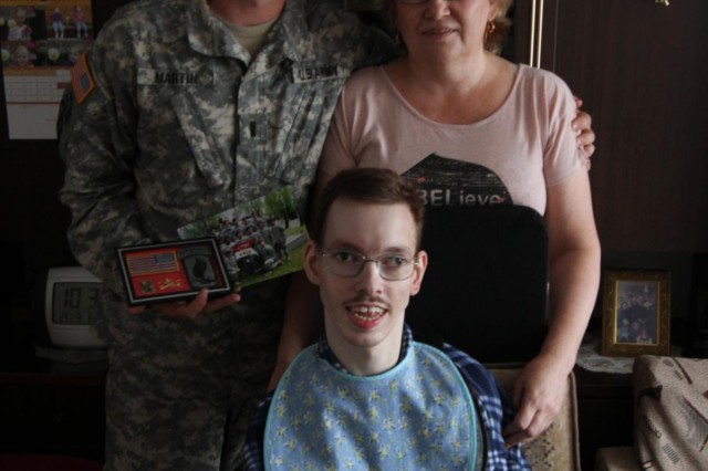 First Lt. Andrew Martin of Nashville, Tenn., 2nd platoon leader for Troop A, 1st Squadron, 91st Cavalry Regiment, 173rd Airborne Brigade, poses with Egidija Gvergzdis and her son Nerijus (left) at her apartment in Kaunas, Aug. 14, 2014. Martin's grandparents, Fred and Valjean Young of Atlanta, sponsored Nerijus, who was born with cerebral palsy , for multiple surgeries in the United States to have his legs uncrossed and his dental issues addressed. Almost 20 years later Martin was deployed to Lithuania for Operation Atlantic Resolve and able to reconnect with Egidija and Nerijus for a brief reunion. The 173rd Airborne is currently deployed to Estonia, Latvia, Lithuania and Poland as part of Operation Atlantic Resolve, an exercise dedicated to demonstrating commitment to NATO obligations and maintaining interoperability with allied forces.