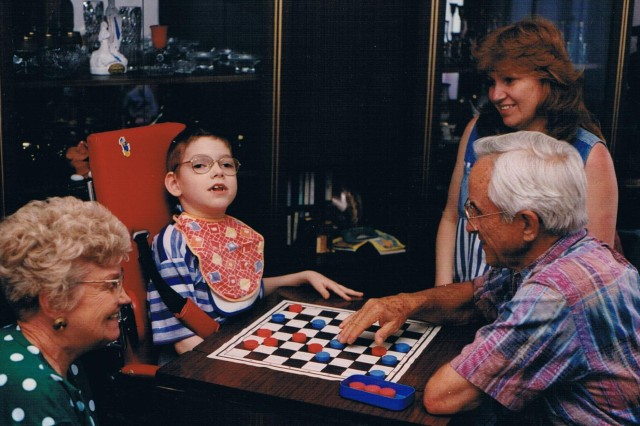 Fred Martin (far right) of Atlanta plays checkers with Nerijus Gvergzdis, while Fred's wife, Valjean (left) , and Nerijus' mother, Egidija (top right), watch on in the family's apartment in Kaunas, Lithuanua. Fred and Valjean, sponsored Nerijus, who was born with cerebral palsy, for multiple surgeries in the United States to have his legs uncrossed and his dental issues addressed. Almost 20 years later their grandson, 1st Lt. Andrew Martin of Nashville, Tennessee, 2nd platoon leader for Troop A, 1st Squadron, 91st Cavalry Regiment, 173rd Airborne Brigade, was deployed to Lithuania for Operation Atlantic Resolve and able to reconnect with Egidija and Nerijus for a brief reunion. The 173rd Airborne is currently deployed to Estonia, Latvia, Lithuania and Poland as part of Operation Atlantic Resolve, an exercise dedicated to demonstrating commitment to NATO obligations and maintaining interoperability with allied forces.