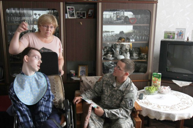 First Lt. Andrew Martin of Nashville, Tenn., 2nd platoon leader for Troop A, 1st Squadron, 91st Cavalry Regiment, 173rd Airborne Brigade, listens as Egidija Gvergzdis shares stories about Martin's grandparents and her son Nerijus (left) at her apartment in Kaunas, Lithuania, Aug. 14, 2014. Martin's grandparents, Fred and Valjean Young, sponsored Nerijus, who was born with cerebral palsy, for multiple surgeries in the United States to have his legs uncrossed and his dental issues addressed. Almost 20 years later Martin was deployed to Lithuania and was able to reconnect with Egidija and Nerijus for a brief reunion. The 173rd Airborne is currently deployed to Estonia, Latvia, Lithuania and Poland as part of Operation Atlantic Resolve, an exercise dedicated to demonstrating commitment to NATO obligations and maintaining interoperability with allied forces.