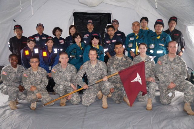 MEDDAC-Japan Soldiers stand with their Japanese Counterparts during the Sagamihara Disaster Drill Sept. 1, 2014. From left to right Spc. Kenya Horton, Pfc. Josue Vaquerano, Pfc. Mark Wilkinson, Capt. Michael Preczewski, Capt. Jino Caro, Pvt. Alisha Crampton,  and Maj. Quentin Rance.