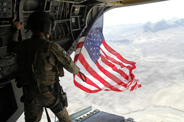 Sgt. Michael Misheff, CH-47F Chinook helicopter chew chief for Task Force Flying Dragons, flies the American flag over southern Afghanistan Aug. 28. Task Force Raptor pilots and crew chiefs fly American flags to present with certificates to service members as part of aviation tradition.