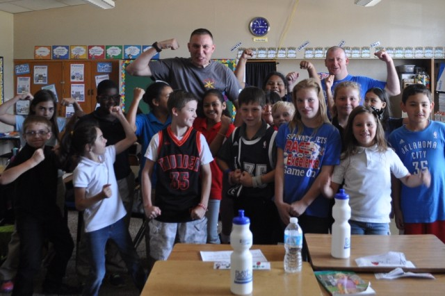 Capt Samuel Flaming and Sgt. Ruark Olson pose with students shortly after the playground dedication.