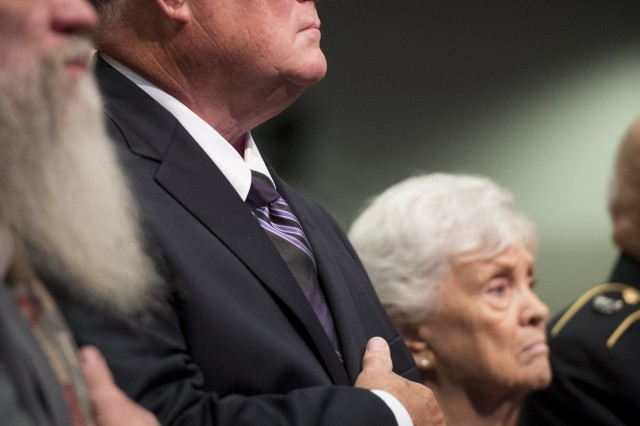 Dr. Bill Sloat places his hand over his heart for the National Anthem during a Pentagon Hall of Heroes induction ceremony, Sept. 16, 2014.  Dr. Sloat is accepting the posthumous Medal of Honor citation and flag on behalf of his brother Spc. 4 Donald P. Sloat.  Sloat received the Medal of Honor (posthumously) at the White House Sept. 15, for his actions in Vietnam, in 1970.