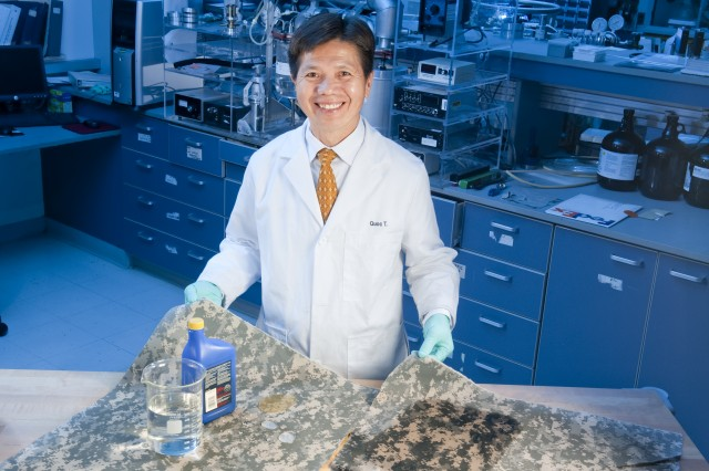 """Natick's Quoc Truong, a physical scientist, provided technical guidance and direction to Luna Innovations, Inc., to successfully develop a durable, """"omniphobic"""" coating used to produce self-cleaning fabrics. Here, Truong demonstrates how the self-cleaning fabric repels liquids better than regular Army Combat uniforms. The technology has now made its way to the commercial market."""