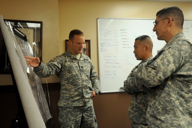"Capt. Jared Graham (left), a Cavalry Leader Course instructor assigned to 3rd Squadron, 16th Cavalry Regiment, 316th Cavalry Brigade, explains mission planning strategy to Capt. James Harrison (center), and Staff Sgt. Arthur Jennings (right), both assigned to 1st Squadron ""Garryowen,"" 7th Cavalry Regiment, 1st Brigade Combat Team ""Ironhorse,"" 1st Cavalry Division, during a Mobile Training Team CLC Sept. 12, at Fort Hood, Texas. Graham came from Fort Benning, Georgia, to instruct nine Garryowen Soldiers during the three-week long class (U.S. Army photo by Spc. Paige Behringer, 1BCT, 1st Cav. Div. PAO)"