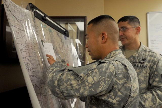 "Capt. James Harrison (left), and Staff Sgt. Arthur Jennings, both assigned to 1st Squadron ""Garryowen,"" 7th Cavalry Regiment, 1st Brigade Combat Team ""Ironhorse,"" 1st Cavalry Division, review a map during a Mobile Training Team Cavalry Leader Course Sept. 12 at Fort Hood, Texas. During week two, the class had to create a plan of action based on a brigade-level order to provide a flank guard in a battlefield scenario. (U.S. Army photo by Spc. Paige Behringer, 1BCT, 1st Cav. Div. PAO)"