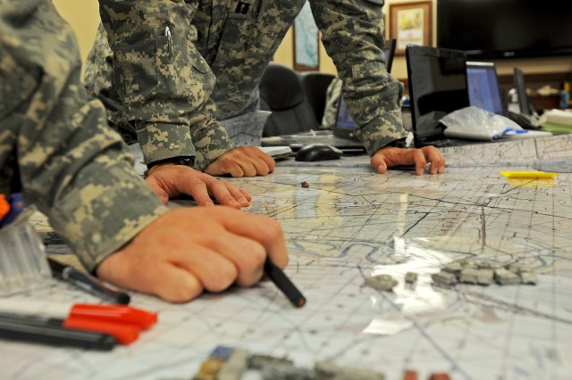 "Soldiers assigned to 1st Squadron ""Garryowen,"" 7th Cavalry Regiment, 1st Brigade Combat Team ""Ironhorse,"" 1st Cavalry Division use a map to plan a simulated mission during a Mobile Training Team Cavalry Leaders Course Sept. 12 at Fort Hood, Texas. ""I consider this a high payoff training event, and it's also low cost, because instead of sending nine students to Fort Benning, the unit only has to pay for one instructor to come to them,"" said Capt. Jared Graham, a Cavalry Leader Course instructor assigned to 3rd Squadron, 16th Cavalry Regiment, 316th Cavalry Brigade. ""I think a unit can get a lot out of the training and the personnel, because now they can understand doctrine and apply it for their unit in a way that's really going to help them be more effective."" (U.S. Army photo by Spc. Paige Behringer, 1BCT, 1st Cav. Div. PAO)"