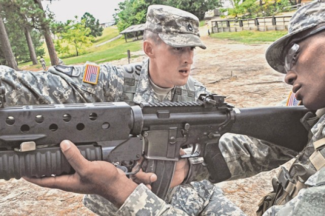 Fort Leonard Wood's Staff Sgt. Jonathan Miller, 787th Military Police Battalion, 14th MP Brigade, teaches a Soldier how to fire an M203 grenade launcher. Miller was competing in and won the U. S. Army Training and Doctrine Command's drill sergeant of the year competition at Fort Jackson, S.C.