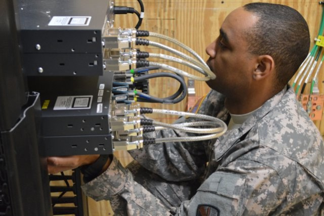 Spc. Shannon January from the 56th Signal Battalion at Joint Base San Antonio-Fort Sam Houston, Texas, holds new switches in place while other technicians fasten them to a rack.