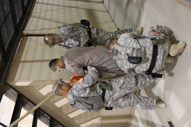 Soldiers assigned to California National Guard's 670th Military Police Company practice handcuffing a detainee role-player in order to take him to a medical appointment as part of a Cumulative Training Exercise at Forward Operating Base Westbrook, McGregor Range, N.M., recently. The 670th MP Co. is training for a deployment to Guantanamo Bay Naval Base, Cuba. (Photo by Maj. Amabilia Payen, 5th Armored Brigade, Division West Public Affairs)