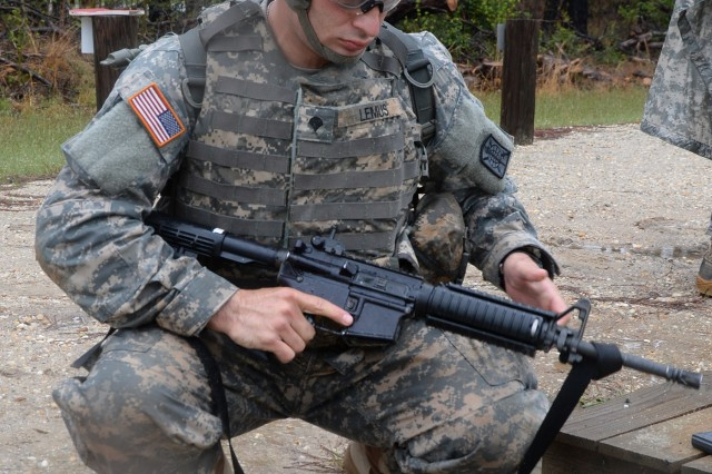 """Spc. Michael Lemus inspects his M-4 Carbine during range qualification training at Fort A.P. Hill, Virginia, April 28. Lemus is a cryptologic linguist with Company D, 715th Military Intelligence Battalion, 500th Military Intelligence Brigade, Schofield Barracks, Hawaii, and the U.S. Army Intelligence and Security Command's and U.S. Army Military District of Washington's """"Best Soldier."""""""