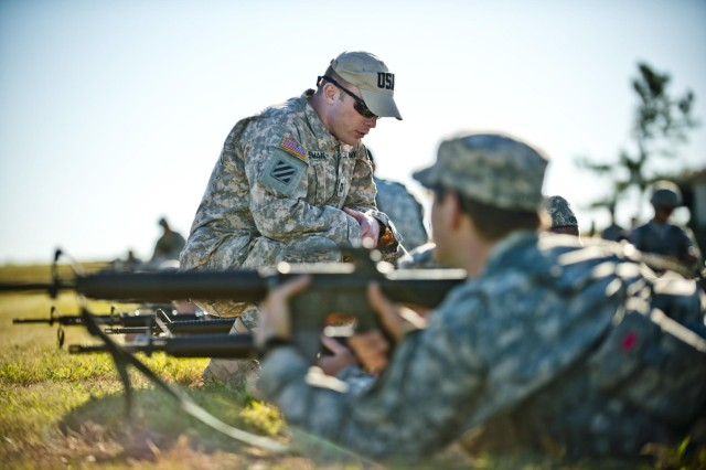 Capt. Samuel Kirk Freeman, an instructor with the Army Reserve Mobile Training Team, coaches a group of competitors on rifle marksmanship before the start of the inaugural Army Reserve Small Arms Championship hosted at Camp Robinson, Ark., Sept. 22, 2014. Approximately 70 Soldiers, comprising 14 teams, came from all over the country to compete.