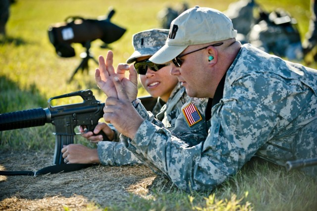 Sgt. 1st Class Kristopher Beerman, a coach and Army Reserve Service Pistol Team shooter, teaches sight alignment and rifle marksmanship to 1st Lt. Jemarie Alcordo, with the 208th Digital Liaison Detachment, from Colorado Springs, Colo., during the inaugural Army Reserve Small Arms Championship hosted at Camp Robinson, Ark., Sept. 22, 2014. Approximately 70 Soldiers, comprising 14 teams, came from all over the country to compete.