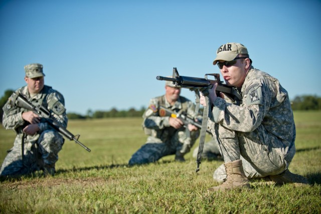 Capt. Samuel Kirk Freeman, an instructor with the Army Reserve Mobile Training Team, shows how to hold a kneeling shooting position to a group of competitors during the inaugural Army Reserve Small Arms Championship hosted at Camp Robinson, Ark., Sept. 22, 2014. Approximately 70 Soldiers, comprising 14 teams, came from all over the country to compete.
