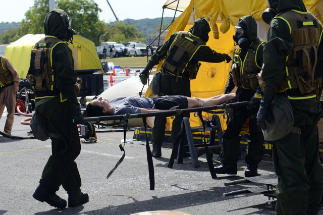Emergency responders move a mock victim through the decontamination line, during a Capital Shield 2015 exercise at Robert F. Kennedy Memorial Stadium, Washington, D.C., Sept. 23, 2014.