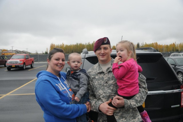 Staff Sgt. Gerald Neal, an intelligence analyst with the 1st Squadron (Airborne), 40th Cavalry Regiment, 4th Infantry Brigade Combat Team (Airborne), 25th Infantry Division, takes a moment for a photo with his Family following the Danali Squadron's deployment ceremony September 19, 2014 at Joint Base Elmendorf-Richardson, Alaska. (U.S. Army photo by Sgt. Brian Ragin/Released)