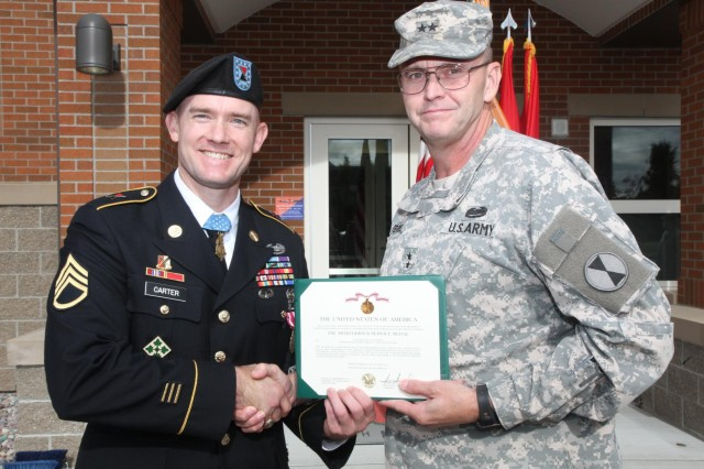 Medal of Honor recipient Staff Sgt. Ty Carter (left), receives a Meritorious Service Medal from Maj. Gen. Terry Ferrell, commander, 7th Infantry Division, during a ceremony, Sept. 26, 2014, at Joint Base Lewis-McChord, Wash.