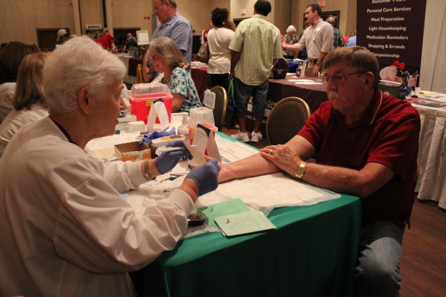 Retired Sgt. 1st Class Tony Jones of Manchester, Tenn., gets his cholesterol and glucose checked by registered nurse Sue Morgan of Huntsville Hospital. The Retiree Appreciation Day health fair, coordinated by Fox Army Health Center, offered several health screenings and health information.