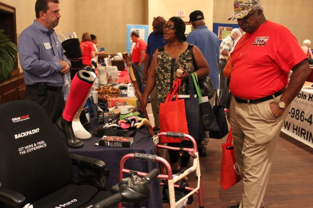 Retired Staff Sgt. Jackie Garnett and her husband, retired Master Sgt. Jerry Garnett, talk with Michael Schotten of McAbee Medical about medical equipment and health products that can be purchased for those suffering from mobility issues.
