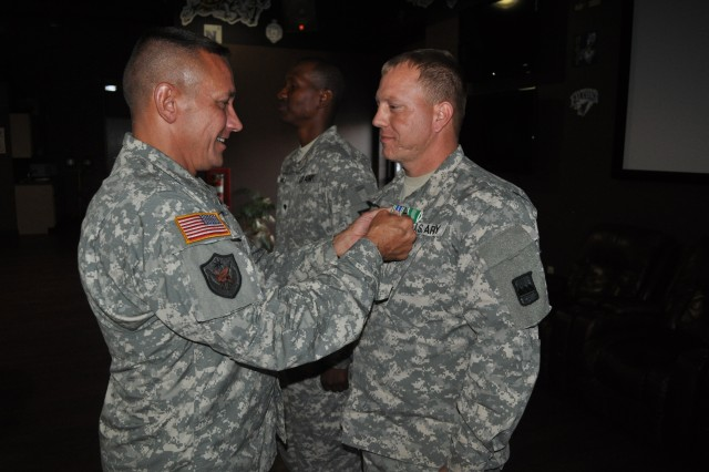 "Col. Clarence Combs, 80th Training Command deputy operations officer, awards the Army Commendation and Achievement medals to Staff Sgt. Jason O'Farrell, C Co, 4/321st Logistical Support Battalion, 800th LSB, who received top honors in the driver and team categories of the brigade's Logistical Training Exercise, also known as a ""Truck Rodeo,"" during an awards banquet at Fort Knox Ky., Sept. 20, 2014. The LTX assesses the competence level of Army truck drivers and wheeled vehicle mechanics regarding their primary missions of providing transportation and maintenance services."