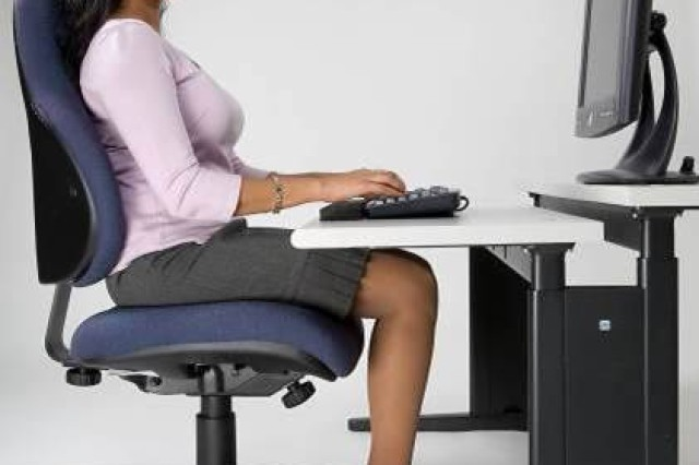 A proper seated position involves feet flat on the floor, shoulders in a relaxed position, and forearms and wrists parallel to the floor according to the U.S. Army Public Health Command's Ergonomics Program.