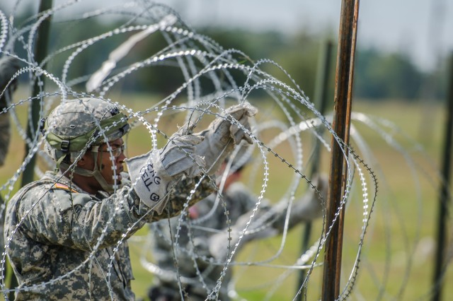 Sgt. 1st Class Eddie Jackson Jr., 1st Brigade Combat Team engineer cell operations sergeant, carefully emplaces concertina wire to create an entry control point for a perimeter surrounding 1st BCT's Tactical Operation Center during the Mountain Peak exercise Monday at Fort Drum.