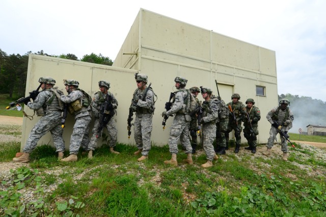 Albanian soldiers and U.S. Soldiers of Bravo Company, 2nd Battalion, 5th Cavalry Regiment, 1st Brigade Combat Team, 1st Cavalry Division (Ironhorse) stack on a wall and prepare to assault during exercise Combined Resolve II at the Joint Multinational Readiness Center in Hohenfels, Germany, May 17, 2014. Ironhorse will return as the Army's rotational force in Europe to participate in Combined Resolve III in Oct-Nov, 2014, as well as providing forces for Operation Atlantic Resolve in eastern Europe. (U.S. Army photo by Spc. Tyler Kingsbury)