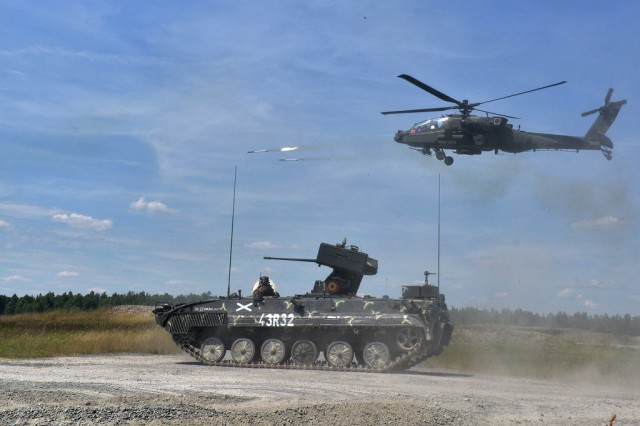 Romanian armored vehicles and U.S. Army AH-64 Apache helicopters conduct a combined arms live fire exercise (CALFEX) at the 7th Army Joint Multinational Training Command's Grafenwoehr Training Area as part of exercise Combined Resolve II, June 27, 2014. The third exercise in the Combined Resolve series will take place Oct-Nov, 2014 at the Grafenwoehr and Hohenfels Training Areas in southeast Germany. (U.S. Army photo by Visual Information Specialist Gertrud Zach)