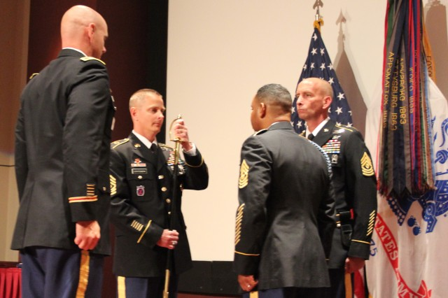 The Garrison's incoming Command Sgt. Maj. Robert Lehtonen II accepts the noncommissioned officers sword from commander Col. Bill Marks, left, to symbolize his assumption of new responsibilities with the Garrison.