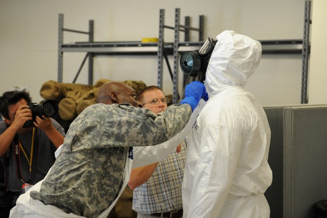 Maj. John Dills (left), the 36th Engineer Brigade chief of current operations, helps zip and close the protective suit of Sgt. 1st Class Venrick James, also from the 36th Eng. Bde., during training inside the Medical Skills Training Center at Fort Hood, Texas, Oct. 9, 2014. Soldiers from the brigade conducted the training in preparation for their upcoming deployment in support of Operation United Assistance, a U.S. government effort to combat Ebola outbreaks in West Africa. The Soldiers trained to work in buddy teams to put on and take off their protective equipment, a measure aimed at minimizing the chance contamination.