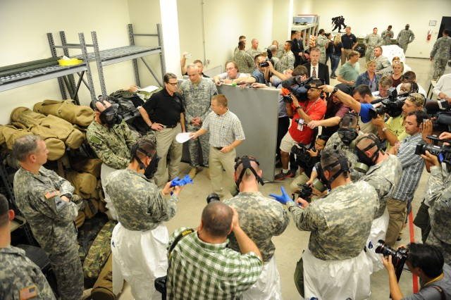 Texas Governor Rick Perry watches as Soldiers of the 36th Engineer Brigade conduct training inside the Medical Skills Training Center at Fort Hood, Texas, Oct. 9, 2014. The Soldiers are training on how to properly put on M40 protective masks, nitrile gloves and Tyvek protective suits as they prepare to deploy in support of Operation United Assistance, a U.S. government effort to combat Ebola outbreaks in West Africa.
