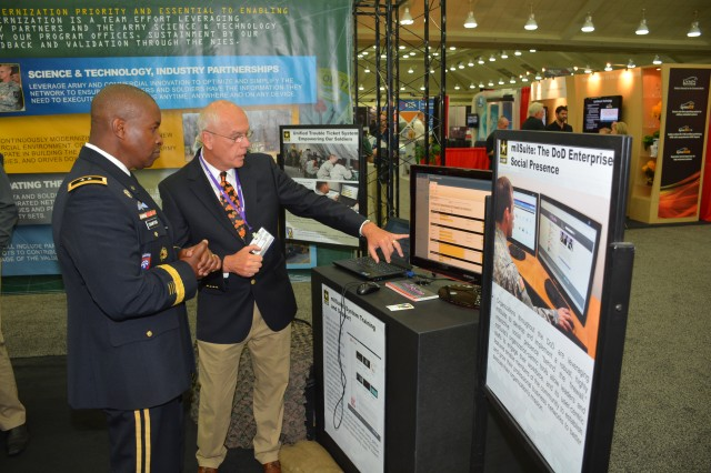 BALTIMORE, Maryland (Oct. 8, 2014) -- Aberdeen Proving Ground Senior Commander and Commanding General of U.S. Army Communications-Electronics Command Maj. Gen. Bruce T. Crawford (left), watches a demonstration of the Unified Trouble Ticketing System by Ray Maxwell from Program Executive Office, Command, Control, Communications-Tactical Military Technical Solutions Office at the Army booth during the Military Communications Conference (MILCOM) at the Baltimore Convention Center.  Crawford led a five-person plenary panel with the topic of 'Fielding the Army Tactical Network.'